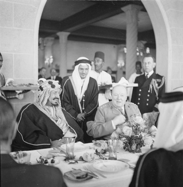 Winston Churchill sits with King 'Abd al-'Aziz Ibn Saud of Saudi Arabia during lunch at Auberge due Lac, Fayoum, in February 1945. The King's interpreter is standing behind him.