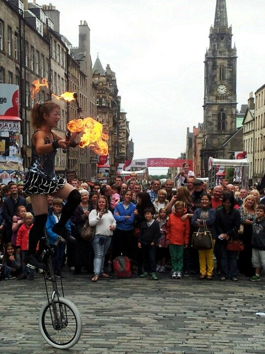 Juggling with fire on a unicycle on cobbles! Street entertainment on the Royal Mile during the Edinburgh Festival Fringe.