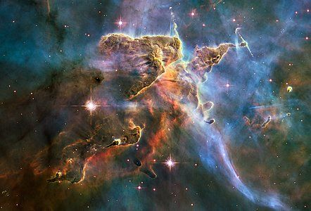 The NASA/ESA Hubble Space Telescope captured this billowing cloud of cold interstellar gas and dust rising from a tempestuous stellar nursery located in the Carina Nebula, 7500 light-years away in the southern constellation of Carina. This pillar of dust and gas serves as an incubator for new stars and is teeming with new star-forming activity.