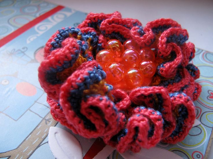 Aranka - háčkovaný 3D květ Nebe se dotýká země. A na tomto místě rozkvétá barevný květ, jen k němu přivonět... Tato květina je uháčkována ze slabých bavlněných přízí (oranžový základ, modrý střed, sytě růžové okraje). Doplněno knoflíčkem osázeným třpytivými perličkami. Má průměr cca 5,5 cm. Možno použít nejen na tašku, ale také ozvláštnit šál ...