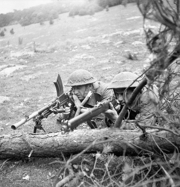 Unidentified infantrymen of The Highland Light Infantry of Canada, who are armed with a Bren light machine gun and a sniper rifle, taking part in a training exercise, England, 11 June 1943.