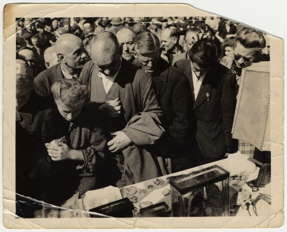 German civilians are forced by Allied soldiers to view a display of tattooed skin and a lampshade made from human skin at Buchenwald.