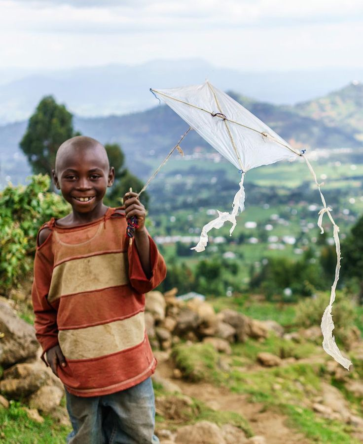 Photo by @ronan_donovan // A young boy proudly displays his homemade plastic kite in the rural village of Bisate, northern Rwanda.  See more from this assignment here, @ronan_donovan