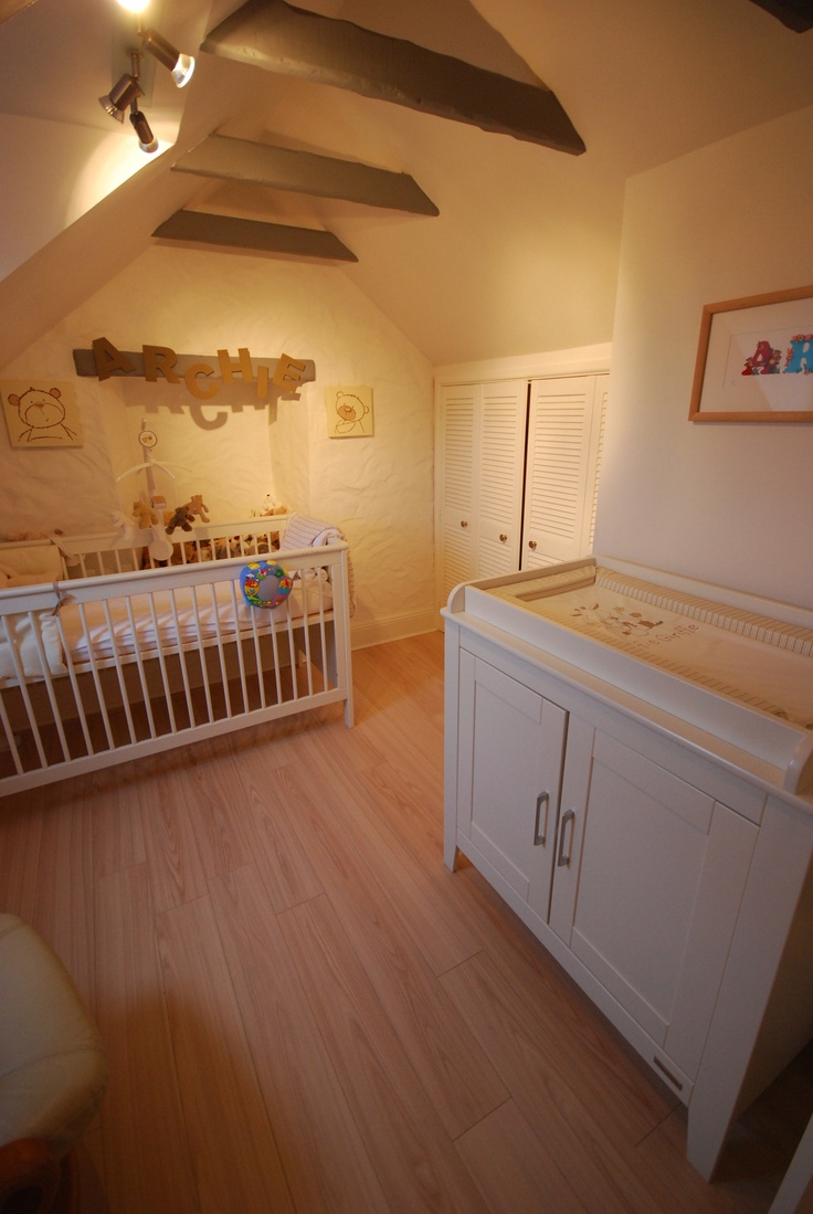 The original beams in this nursery were painted a charcoal grey, ash flooring was installed and the whole room and ceiling was painted white to lift the feeling of this small attic room. Track lighting was installed with movable fixtures.