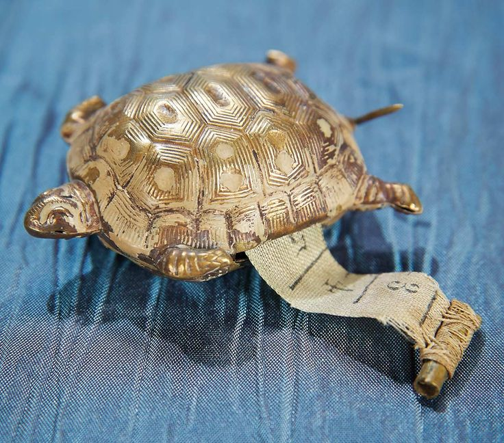 """19TH CENTURY BRASS TAPE MEASURE IN THE SHAPE OF A TURTLE 2"""" (5 cm.) The brass turtle hides a cloth centimeter tape measure in its body which can be rewound by turning its tail.   Late 19th century."""