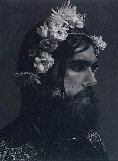 Male muse, Edwardian era headshot of man with beard and flowers in his hair.