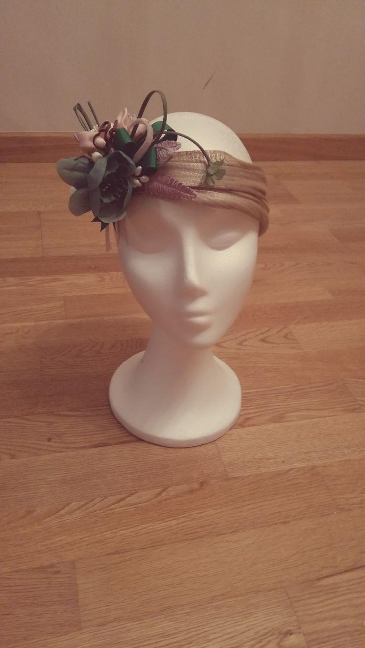 Turbante sinamay de seda dorado con flores de seda verde y rosa, hojas de terciopelo y porcelana fría