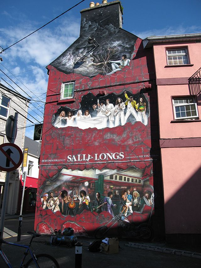 This is a huge mural on the gable wall of Sally Longs in downtown Galway, Ireland. There's Elvis up in heaven pointing a finger at God in a nod to Michelangelo's famous painting on the ceiling of the Sistine Chapel. Art by Ciarán Dunlevy (born 1981) who is specialising in portrains, murals, sign writing, custom airbrushing, window painting, fine art and photography. Visit his website: http://www.dunlevyart.com/index.php