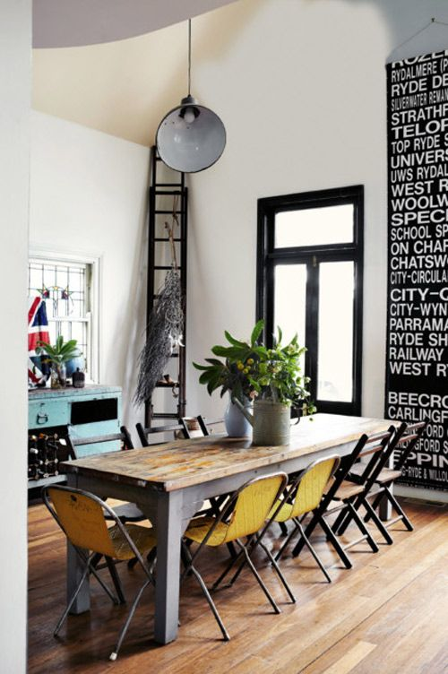 Great dining room with mismatched chairs, a busy scroll and an amazing black framed window.