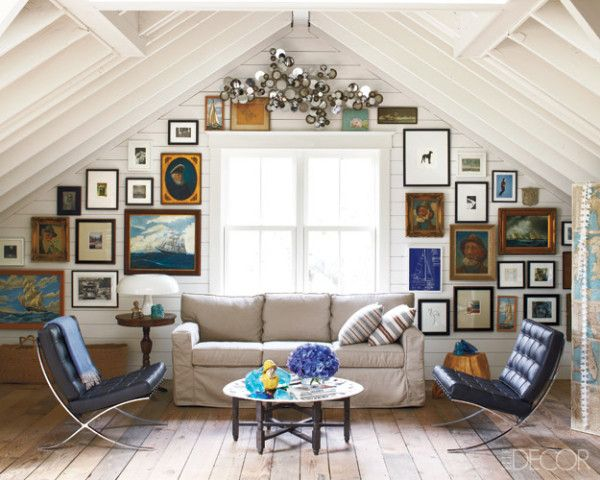 White cathedral ceiling with wide plank aged wood floors, and cute wall gallery around the window behind the couch.