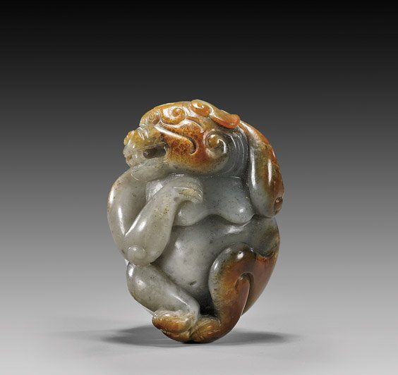 """Charming and beautifully carved, early Chinese multicolor jade model; of a bear scratching its head: the pebble form of gray and black with a good russet skin to the verso; probably Yuan Dynasty; H: 2 3/8""""; Provenance: illustrated in Oriental Art magazine, vol. XLVI, No. 2, pg 92, 2000"""