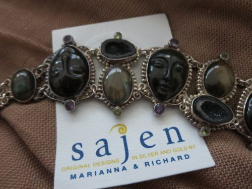 """Sajen Goddess Jewlery Bracelet Sajen Silver by Marianna and Richard Jacobs Multigem """"Goddess"""" Bracelet Sajen's signature """"goddess face"""" carved beautifully, brings a bit of mystery and intrigue to your jewelry collection. Paired with lush labradorite, these ebony beauties create a unique statement piece. •Sterling silver bracelet has oval, moonstone, labradorite and other multi-gem stones station at center  •Center linked to 3 carved """"goddess face"""" stations  •""""Faces"""" set in pear-shaped frames"""