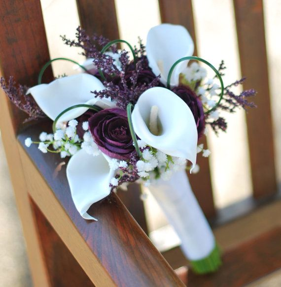 Lovely silk calla lily and plum ranunculus with purple heather and bear grass loops.