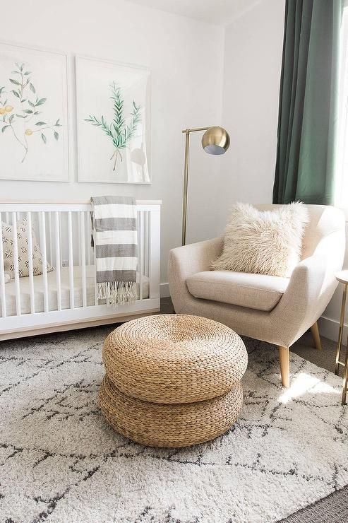 White and green nursery features botanical prints placed over a Babyletto Scoot 3-in-1 Convertible Crib with Toddler Rail draped in a gray striped throw blanket placed atop a black and white Moroccan rug.