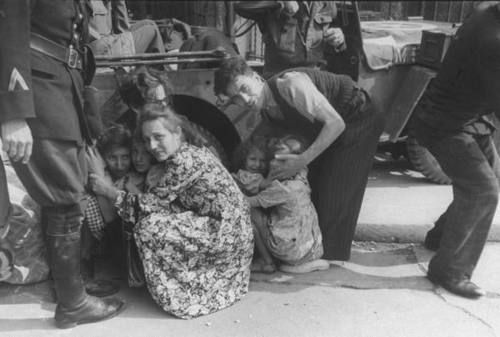 A soldier stands protectively over a frightened French family during a German sniper attack. The sniper attacked while French General Charles DeGaulle was taking a tour of city following its liberation by Allies after uprising of the French Forces of the Interior (F.F.I.) 25 August 1944