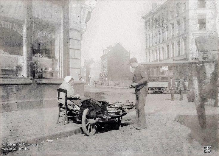 Een visventster heeft haar kar opgesteld aan de Scheldestraat voor de handelszaak Petit Musée uitgebaat door Bruyninckx, rechts café Roels. Klanten komen aangelopen voor sprot en garnalen-1894