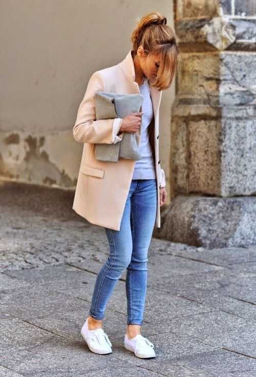 Rock a nude coat with blue slim jeans to effortlessly deal with whatever this day throws at you. White low top sneakers will add some edge to an otherwise classic look.  Shop this look for $123:  http://lookastic.com/women/looks/low-top-sneakers-skinny-jeans-long-sleeve-t-shirt-clutch-coat/5593  — White Low Top Sneakers  — Blue Skinny Jeans  — Grey Long Sleeve T-shirt  — Grey Suede Clutch  — Beige Coat