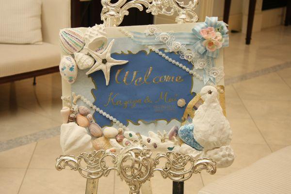 手作りのウェルカムボードは、貝殻などのモチーフがたくさん!ベースの色をマリンブルーにしたのも素敵です。