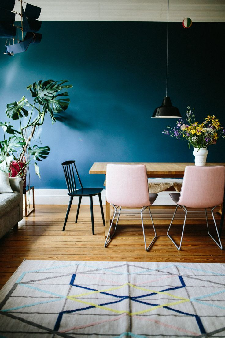 Deep teal walls and blush pink chairs in modern dining room with moody vibe. Love all the plants!