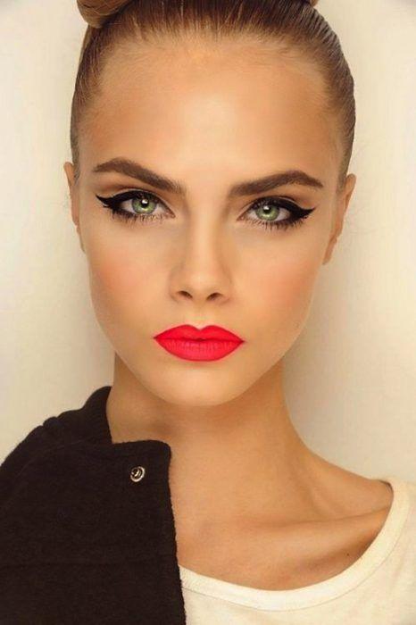 Chica usando un lápiz labial de color coral neón