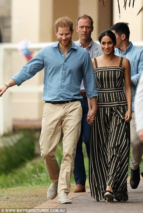 dc93816a3 Meghan cradles her baby bump as she and Harry kick off shoes on ...