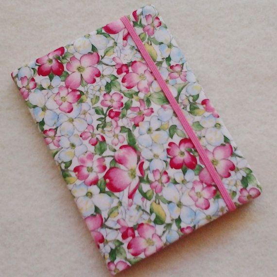 Este es una encantador poco hecho a mano batik notebook cubierta, hecha con un algodón hermoso impresión que presenta flores de color rosa y blanco Cornejo. Tan bonita! Este elegante, uno de una clase, funda extraíble ajusta a un 4-1/2 x 3-1/4 composición mini portatil, que se incluye. Las aletas interiores dobles bolsillos para efectivo, tarjetas de débito, recibos, etc. y un guarda de cierre elástico todo seguro. Forrado a tela teñida a mano.  --Protege su libro de memo en estilo…