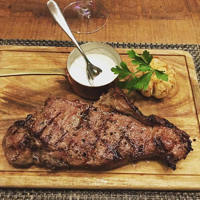 US prime Striploin Steak cooked in Josper coal grill oven, roasted garlic, musta. by.chef Ian Kittichai