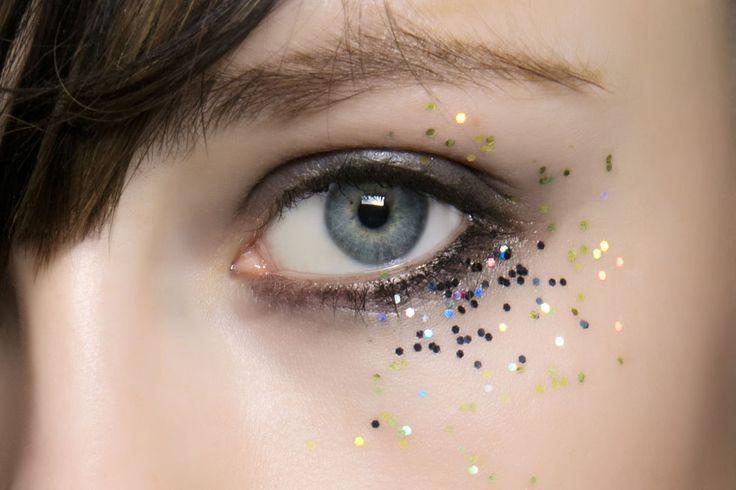 Trucca gli occhi con un ombretto grigio e dai luce picchiettando all'angolo esterno piccole paillettes colorate.
