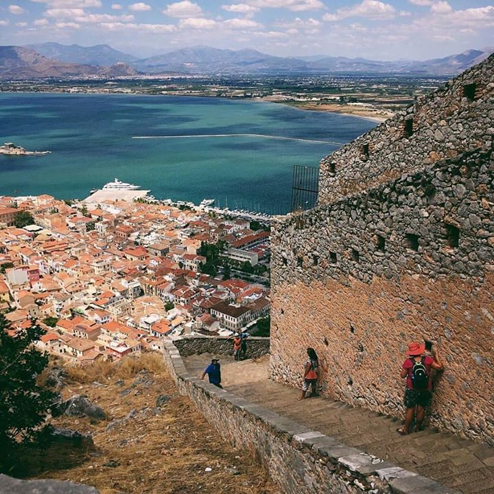 990 - the number of stairs  one needs to climb to reach  the 17th century Venetian  fortresss in Nafplio.   The  charming Old Town of  Nafplio lies below framed by  a perfect blue sky and the  clear aqua water of the  Argolic Gulf.   #stairway #history #stairs #nafplio #palamidi #breathtaking #climbing #peloponnese #travel #greece #clouds #whataview #vsco #iphone #beautifulgreece #familyvacay #travelgreece #travelwithkids #reasonstovisitgreece #handofgreece