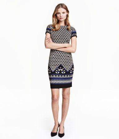 Een nauwsluitende jurk van tricot met een structuurdessin. De jurk heeft korte mouwen, een naad in de taille en een zichtbare ritssluiting achter. Ongevoerd.