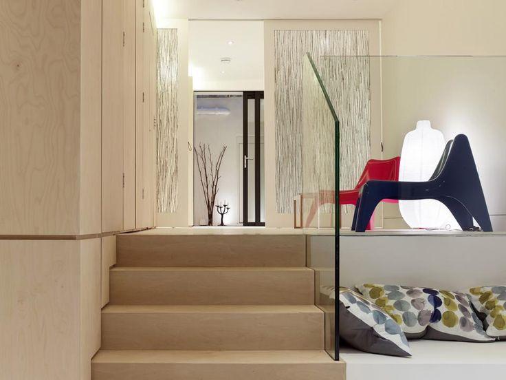 Un seminterrato per due a Londra. L'uso abbondante di pannelli in betulla per mobili e rivestimenti rende gli interni dell'abitazione londinese equilibrati e protetti. Nel living si accende una nota di blu e rosso con la coppia di poltroncine PS Vago di Ikea. Per terra, morbidi cuscini di Habitat.
