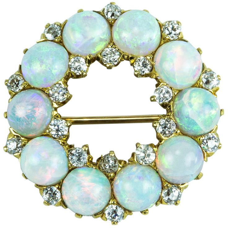 Circa 1900 Edwardian Circle of Fiery Opals accented by Diamonds and set in 18k gold.