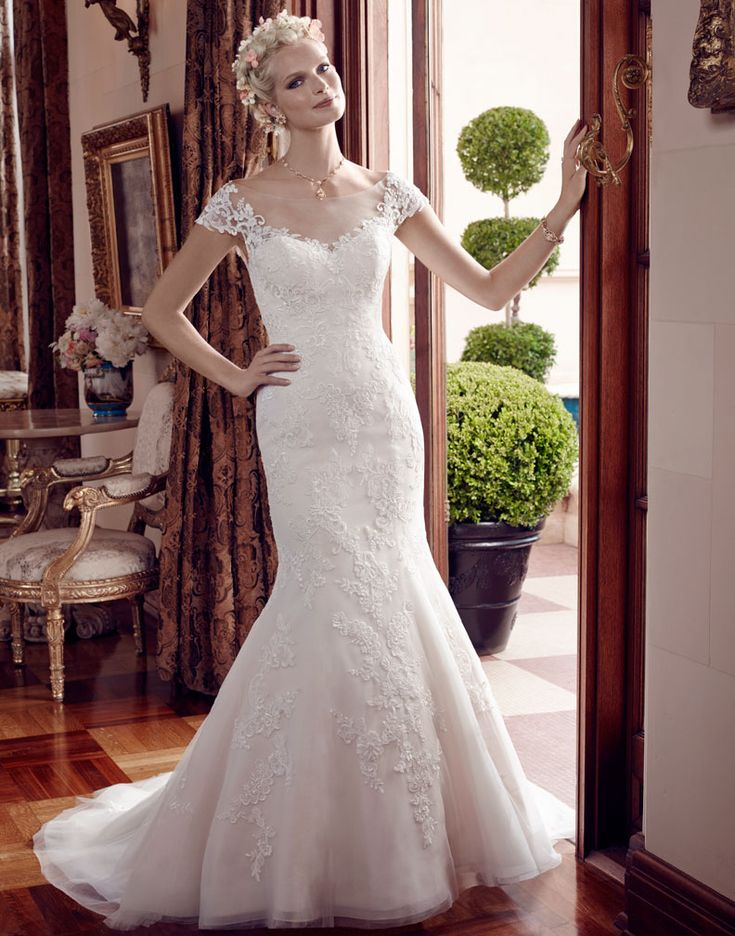 """2192 Mermaid shaped gown is made of non-beaded lace appliqués on Soft Tulle over organza. The illusion front neckline and """"V"""" back neckline feature cap sleeves. The sweetheart satin front neckline is accented with an organic trim of lace appliqués. Horsehair trim finishes the entire hemline of the skirt."""