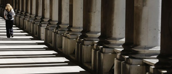 Need to boost your creativity? Just procrastinate.   A woman walks through shadows cast by columns at the Old Royal Naval College in Greenwich east London June 10, 2014.