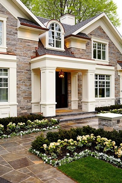 Cheerful traditional home with substantial columns and trim  in warm white