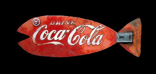 Coke Fish. Cut out of the door of an old Coke machine.  The eye is made up of a gear, Coke bottle cap and a carriage bolt.  In the tail area is the machines coin slot.  Jim Shores