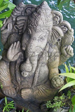 image of ganesh statue standing between plants
