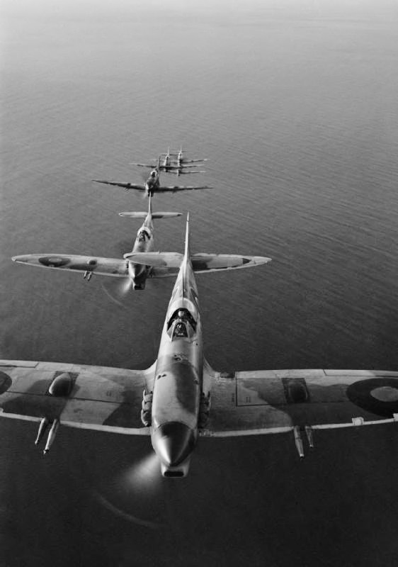 Supermarine Spitfire Mark VCs of No. 2 Squadron SAAF based at Palata, Italy, flying in loose line astern formation over the Adriatic Sea while on a bombing mission to the Sangro River battlefront.  383