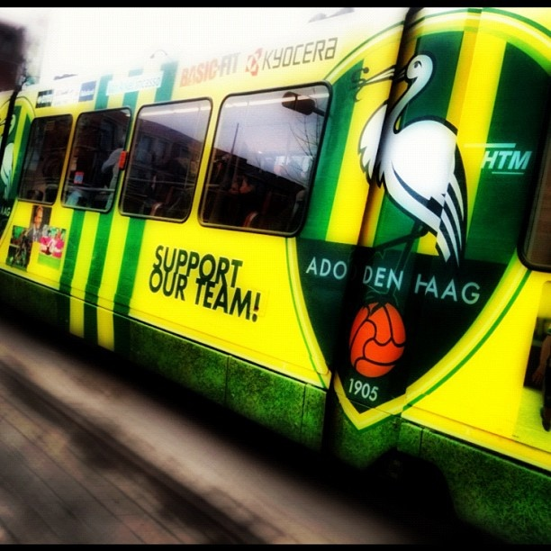 A picture of a tram in The Hague (in The Netherlands) decorated with the local soccer club's logo and promo. ADO Den Haag.