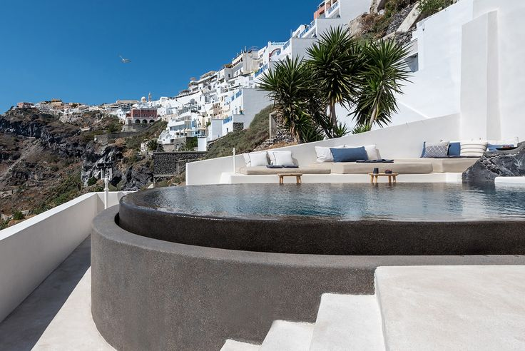 Looking and and across the black infinity swimming pool into the iconic Santorini villas on the cliff face - aboratorium renovate seven suites at Porto Fira luxury hotel in Santorini, Greece. Luxury hotel designs feature on the www.martynwhitedesigns.com interior design blog.