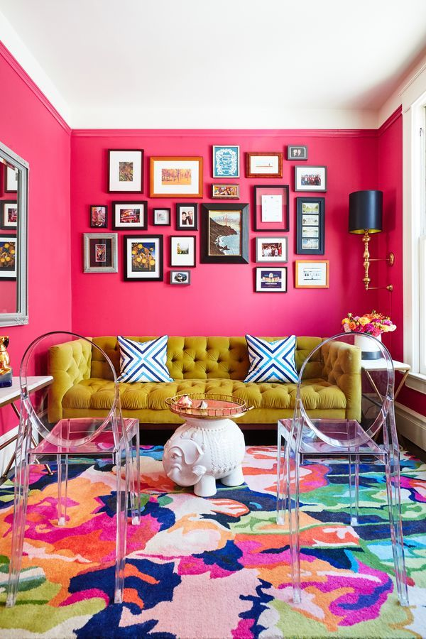 A living room with bright pink walls.