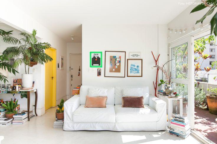 Apê com jeito de praia tem muitas plantas, sofá branco, móveis garimpados e porta pintada de amarelo.