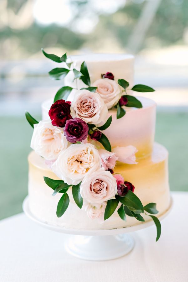Three tier ombre gold, cascading floral wedding cake: http://www.stylemepretty.com/texas-weddings/buda-texas/2016/12/19/rustic-elegant-texas-wedding-full-of-love/ Photography: Julie Wilhite - http://juliewilhite.com/