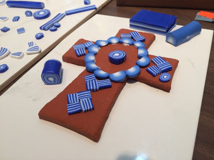 Blue and white on terracotta polymer clay cross in progress. By Pat Brown