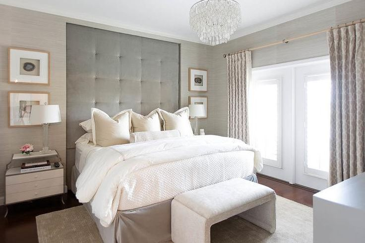 Beautiful refined gray bedroom boasts walls clad in tan grasscloth wallpaper framing a tall gray velvet tufted inset headboard complementing a bed dressed in a gray bedskirt and white and tan bedding accented with white and tan hotel shams.