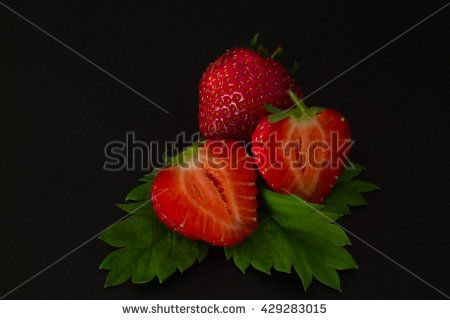 ripe cut in strawberries on a black textural background.toned photo - stock photo