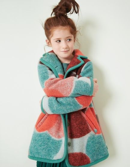 Rijk uitgewerkte winterjas met gekleurde vlakken. De jas sluit met knopen en is afgewerkt met kleurrijke stiksels.