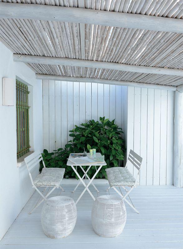 En una de las galerías, al amparo del techo de cañas pintadas  de blanco, una mesa de hierro plegable y dos bancos dobles, todos de la India, crean un comedor de diario en exteriores. Una pareja de bancos de rattan (Lejano Oriente) se suman a la escena.