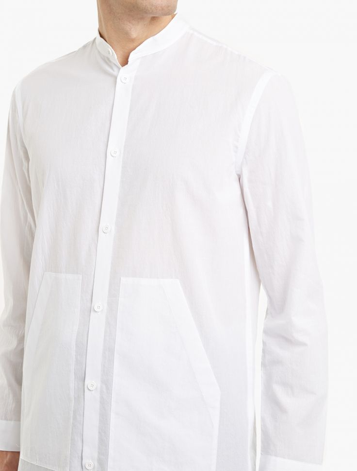 The Helmut Lang Cotton Collarless Shirt for SS17, seen here in white.  Crafted from premium cotton and cut to offer a slim fit, this collarless shirt from Helmut Lang is finished with a button-down closure and an elongated hem.