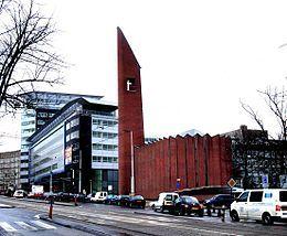 De Opstandingskerk, beter bekend als de 'Kolenkit', aan de Bos en Lommerweg met daarachter het bruggebouw.